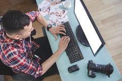 键入在他的计算机上的年轻摄影师在照相讲席会以后 免版税库存图片