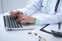 键入在便携式计算机上的一位女性医生的特写镜头,坐在桌上在医院 库存照片