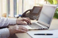 键入在便携式计算机上的手在办公室 免版税图库摄影
