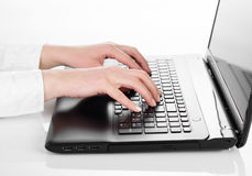 键入在便携式计算机上的手 免版税库存照片