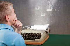 键入在减速火箭的打字机的逗人喜爱的小男孩 图库摄影