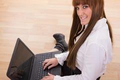 键入在地板上的膝上型计算机键盘的微笑的女商人 库存图片