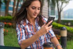 键入在她的手机的被集中的少妇一个正文消息户外 使用智能手机的严肃的女性 库存照片