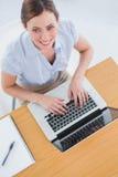 键入在她的膝上型计算机和微笑对照相机的女实业家 免版税库存图片