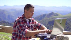 键入在山背景,缓慢的mo的膝上型计算机的人自由职业者的画象 影视素材