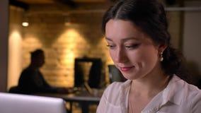 键入在工作场所的膝上型计算机的年轻可爱的成功的女性办公室工作者特写镜头画象  股票录像