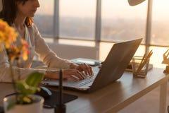 键入在工作场所的被集中的女性雇员使用计算机 工作在个人计算机家的撰稿人的侧视图画象 免版税库存图片