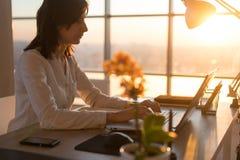 键入在工作场所的被集中的女性雇员使用计算机 工作在个人计算机家的撰稿人的侧视图画象 免版税库存照片