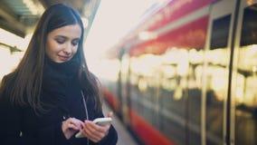 键入在平台的智能手机在火车附近和微笑对照相机的少女 股票录像