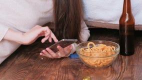 键入在手机的一则消息,吃芯片和喝啤酒的少妇 特写镜头手 股票视频