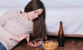 键入在手机的一则消息,吃芯片和喝啤酒的年轻美丽的深色的妇女 免版税库存照片