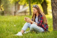 键入在手机的可爱的微笑的女孩在夏天城市公园 有智能手机的现代愉快的妇女,室外 免版税图库摄影