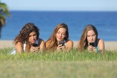 键入在手机的小组三个少年女孩说谎在草 免版税库存图片