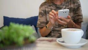 键入在手机的年轻行家妇女在咖啡店 有巧妙的电话的女孩在咖啡馆 慢动作的HD 泰国 影视素材