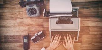 键入在打字机的女实业家由葡萄酒照相机和电话 免版税库存照片