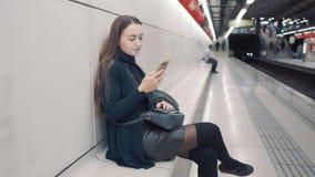 键入在智能手机的妇女在地铁 等待的火车 影视素材