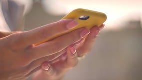 键入在智能手机的妇女的手在晴天在夏天,通信概念,弄脏了背景,侧视图 影视素材