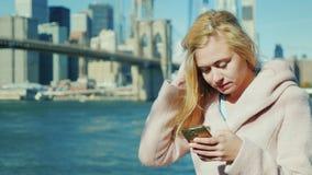 键入在智能手机的少妇 以布鲁克林大桥和曼哈顿地平线为背景在纽约 股票视频