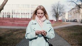 键入在智能手机的愉快的白种人30s妇女 相当时髦白肤金发发短信,当走在城市时 慢的行动 股票录像