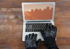 键入在有一个屏幕的膝上型计算机的手有在木桌上的城市大厦的 免版税库存照片