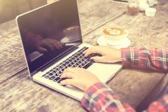 键入在有一杯咖啡的一台膝上型计算机的妇女 库存图片