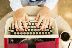 键入在有一杯咖啡的老打字机的女孩户外 免版税库存照片