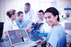 键入在有后边她的队的键盘的美丽的微笑的医生的综合图象 库存照片