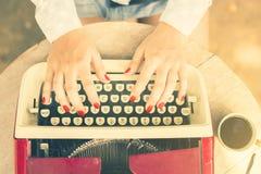 键入在有咖啡的一台打字机的妇女 免版税图库摄影
