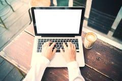键入在有咖啡的一台膝上型计算机的女孩户外 图库摄影
