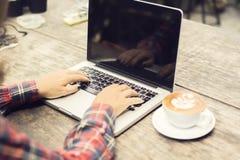 键入在有咖啡的一台膝上型计算机的妇女在早晨 免版税库存照片