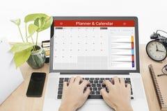 键入在有日历计划者的一个膝上型计算机键盘的企业手 免版税库存图片