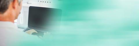 键入在有模糊的绿色转折的膝上型计算机的人 免版税库存图片