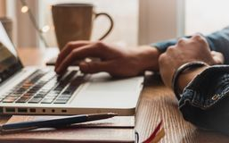 键入在有铅笔、咖啡杯和笔记薄的膝上型计算机的人 库存照片