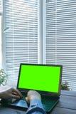 键入在有绿色屏幕的一台膝上型计算机的手 免版税图库摄影