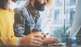 键入在桌面键盘的有胡子的人在一个晴朗的办公室在窗口附近 年轻工友谈论企业想法在 免版税图库摄影