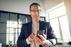 键入在电话的兴旺的商人戴着眼镜消息 库存图片