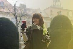 键入在电话的妇女在公园 免版税库存图片