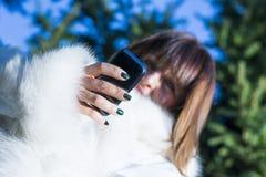 键入在电话的妇女在公园 免版税库存照片