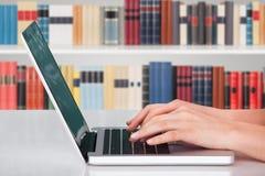 键入在笔记本的手在图书馆里 免版税库存照片