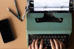 键入在老绿色泰国打字机的手 免版税库存照片