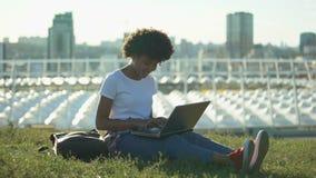 键入在膝上型计算机个人计算机的好非裔美国人的女生户外,自由职业者 影视素材