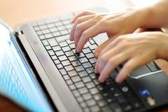键入在膝上型计算机个人计算机键盘的女性手 免版税库存图片