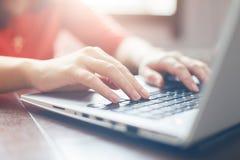 键入在膝上型计算机冲浪的互联网键盘和短信的朋友的女性手通过社会网络,坐在室内木桌上 库存照片