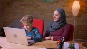 键入在膝上型计算机和他的回教母亲的小男孩hijab的观察他的活动附近坐 股票录像
