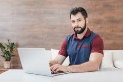 键入在膝上型计算机和在家看照相机的有胡子的人 免版税库存照片