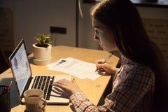 键入在膝上型计算机和签字在docum的千福年的女性雇主 图库摄影