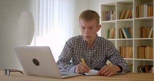 键入在膝上型计算机殷勤地和做笔记的白种人商人画象是繁忙的在书架背景 股票视频