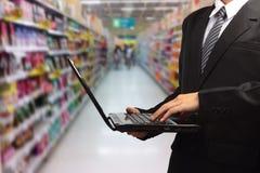 键入在膝上型计算机的人在模糊的超级市场 图库摄影