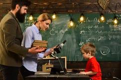 键入在膝上型计算机的企业家庭教师在工作场所在教室,回到学校,学习与书的大学生 免版税图库摄影