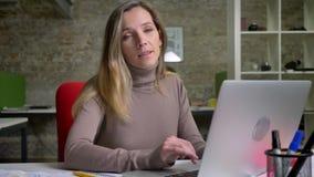 键入在膝上型计算机的可爱的白种人fwemale办公室工作者特写镜头画象偶然地转向照相机和 股票视频